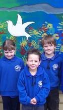 Collinsvale Primary School students and their 'caring and sharing' mural